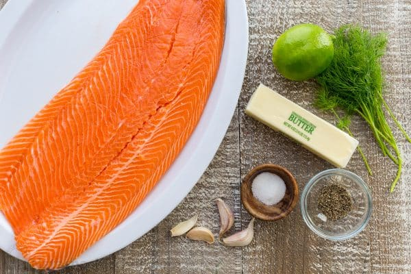 Salmon recipe ingredients with skin-on-salmon filet, lime, butter, garlic, and dill