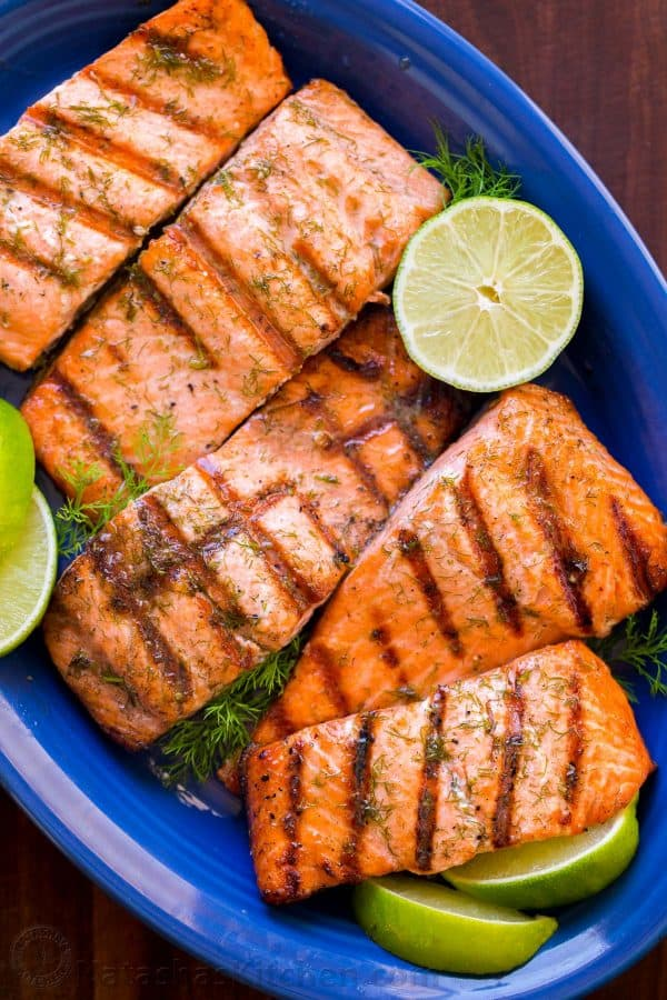 Grilled salmon on platter with lime and dill