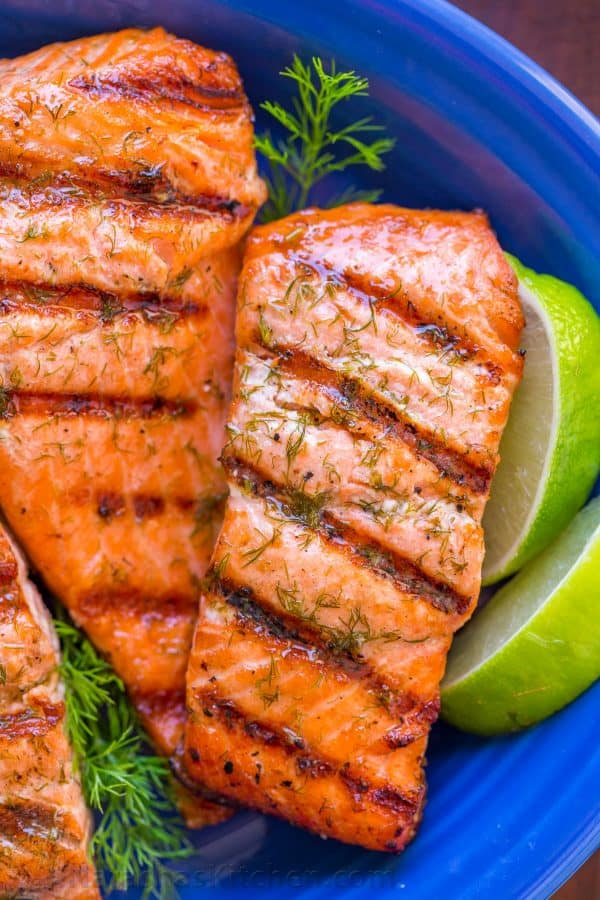 Perfectly Grilled salmon filets drizzled with garlic lime butter and served with lime wedges