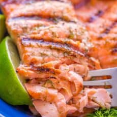 Grilled salmon on a blue plate flaked with a fork