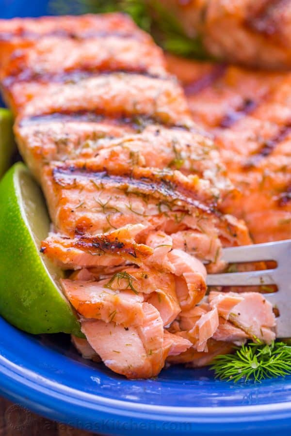 Flaked grilled salmon on a plate with lime
