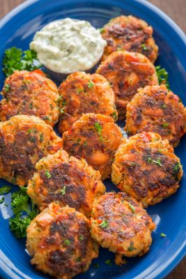 A blue plate with Salmon cakes garnished with parsley and a small bowl of tartar sauce