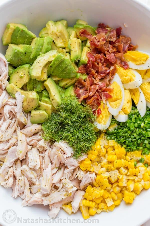 Chicken Salad Recipe in a bowl with avocado, corn, bacon, dill, chives and egg for the best chicken avocado salad