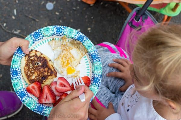 A plate with eggs, pancakes, and strawberries and a little girl