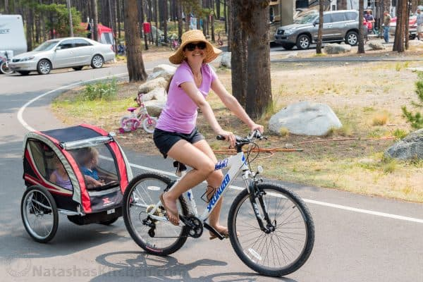 Natasha riding a bike and with a bicycle trailer attached