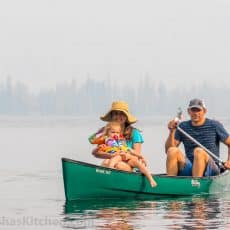 Natasha, her husband, and daughter in a green canoe in a body of water