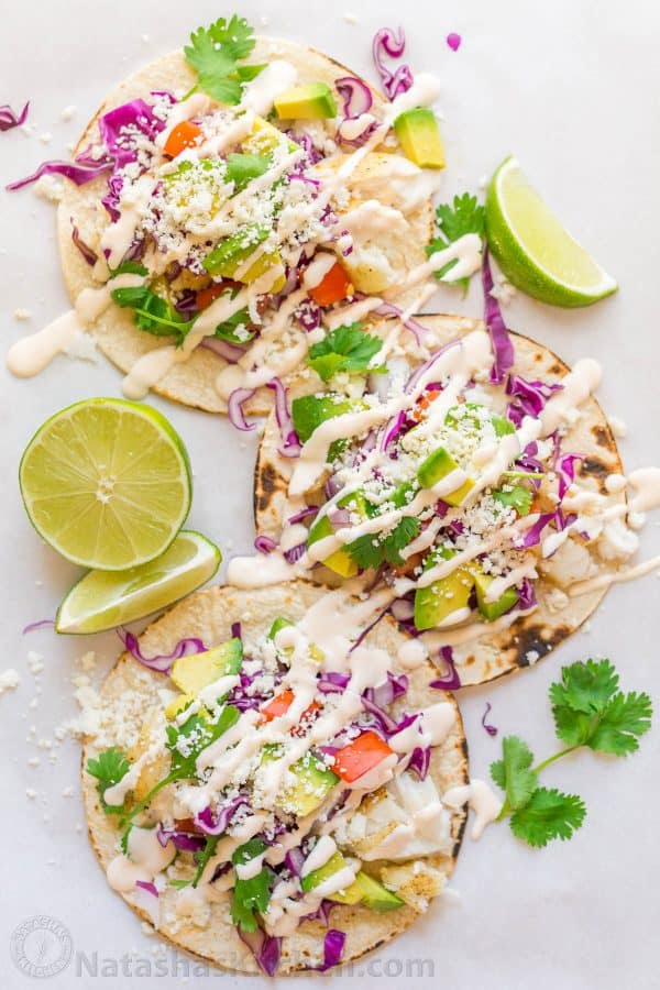 Our go-to fish tacos recipe for entertaining! Easy, excellent fish tacos with the best fish taco sauce; an irresistible lime crema! | natashaskitchen.com