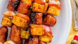 Grilled pineapple sausage skewers that are sweet, spicy, smoky and so flavorful! You won't believe the easy glaze. Easy, excellent brunch skewers recipe.   natashaskitchen.com