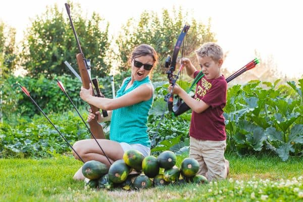 Natasha and her son making silly faces while collecting zucchini