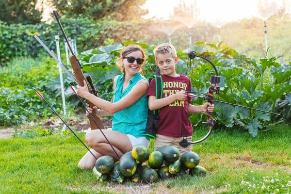 Natasha and her son posing with a crossbow and collecting zucchini