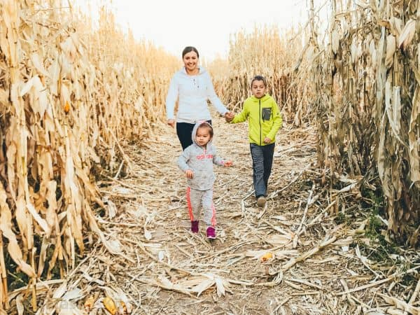 Natasha and her two children walking through a corn maze