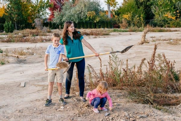 Natasha and her son shoveling dirt and her daughter playing with it