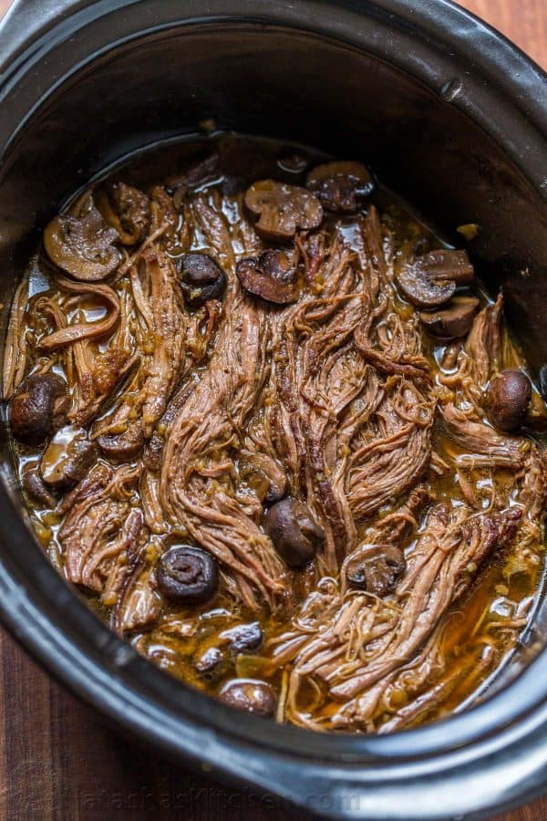 Slow Cooker Beef Brisket is fall-apart tender, juicy, flavorful and easy! The only Slow Cooked beef brisket recipe you'll need! Serve as a side or in a bun. | natashaskitchen.com