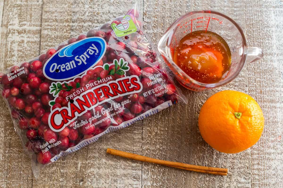 Ingredients with fresh cranberries, honey, cinnamon and orange