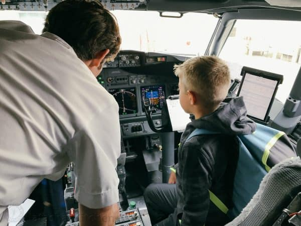 A boy in the cockpit with a pilot