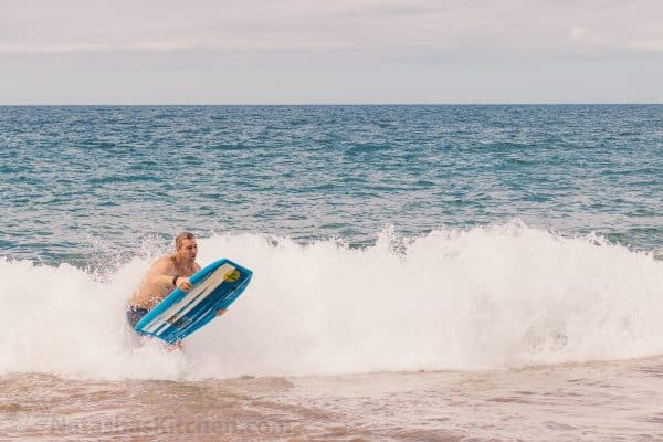 A man riding a wave on a Boogie board in the ocean