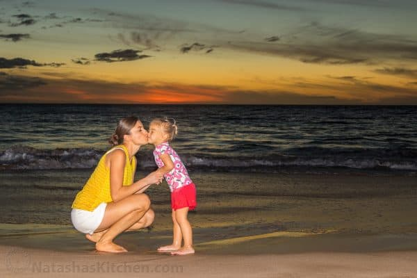 Natasha kissing her daughter on the beach at sunset
