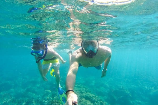 A father and son swimming underwater with scuba gear