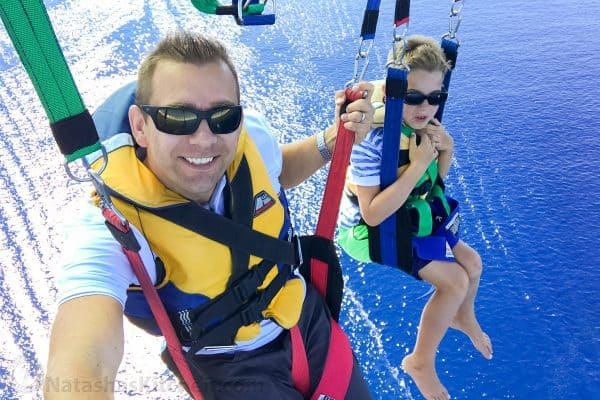 A father and son parasailing over an ocean