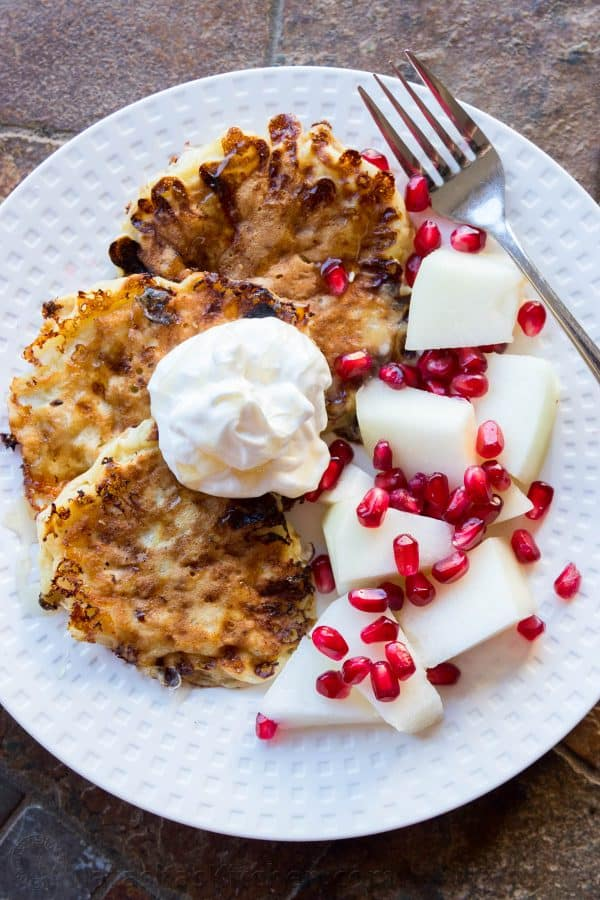 Pancakes on a plate with pears, pomegranate seeds, and whipped cream