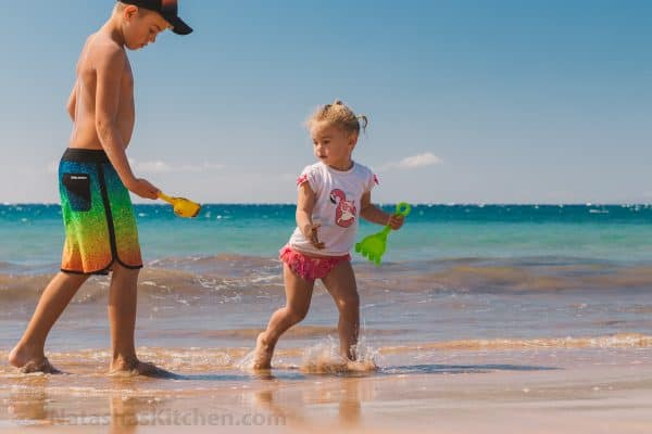 A boy and girl playing in the sand with shovels near the ocean
