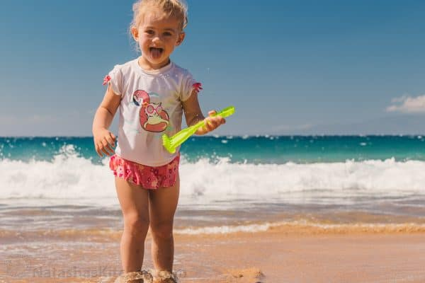 A little girl playing at the ocean with a plastic toy rake