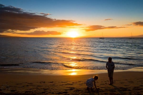 Two children playing at the beach at sunset
