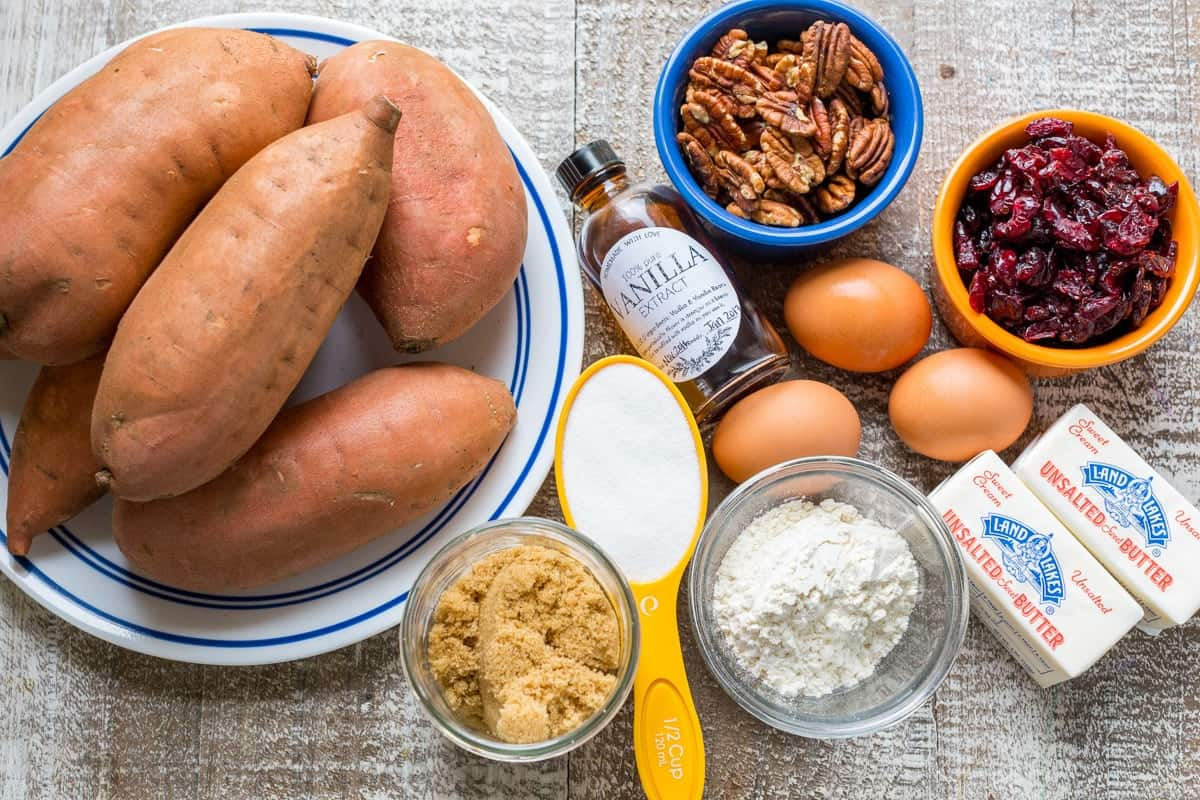 Ingredients for sweet potato casserole with sweet potatoes, eggs, craisins, pecans, sugar topping and butter
