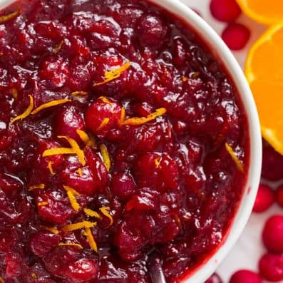 Cranberry sauce recipe served in bowl garnished with orange zest