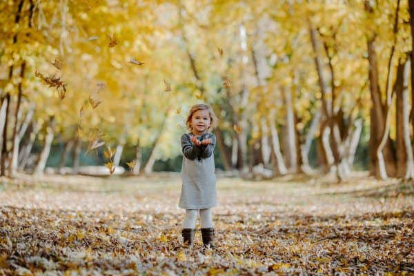 A little girl that is standing and playing in the leaves