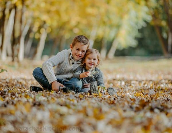 Two children sitting in leaves at the park