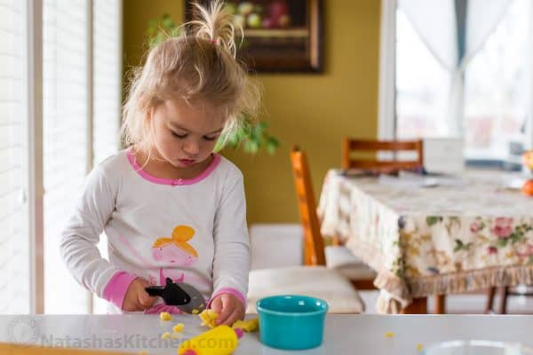 A little girl sitting at a table playing with play dough
