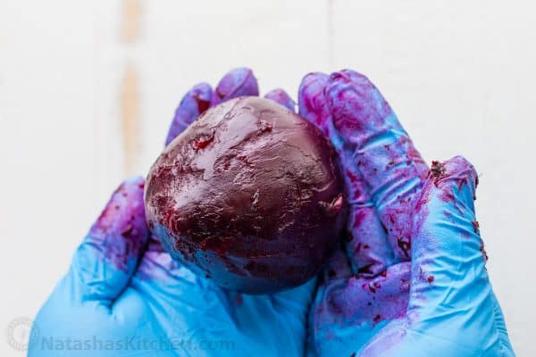 A close up of cooked beet begin held with gloved hands