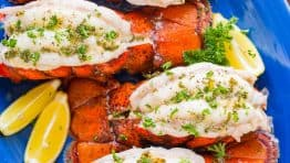 Broiled lobster tails on blue platter