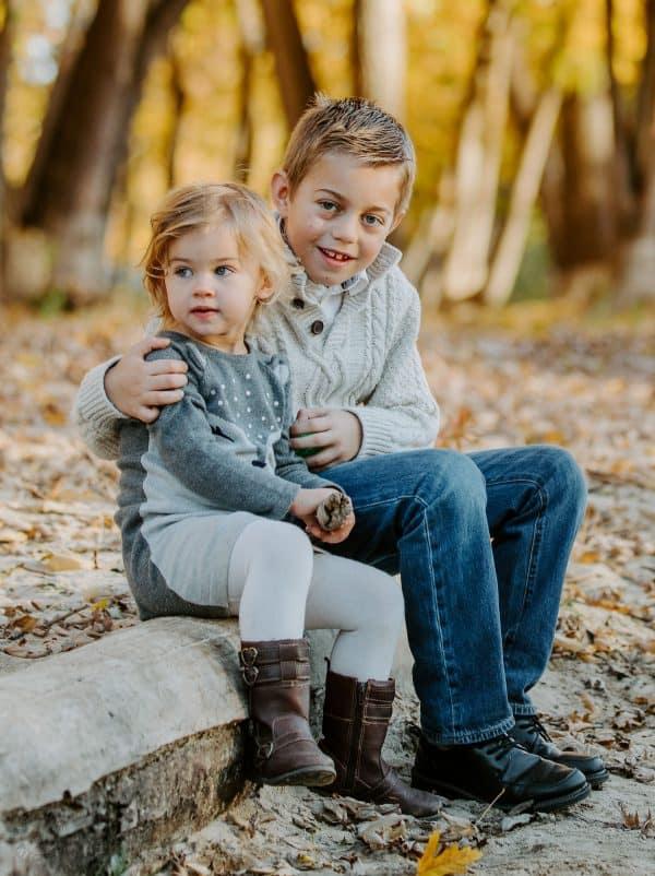 Siblings sitting on a tree log hugging
