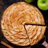 This Apple Tart is a looker! It's crowned with a beautiful rose pattern of sliced apples (and it's easier than you think!). The juices from the cinnamon-sugar coated apple slices, bake into the buttery soft crust. This apple rose tart is lightly sweet and completely irresistible. | natashaskitchen.com