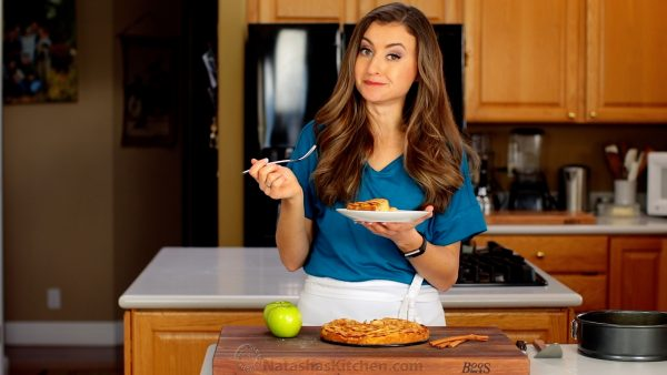 Natasha Kravchuk standing in a kitchen holding a plate with a slice of Apple Tart