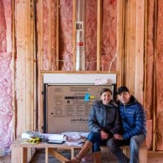 A couple sitting inside a house that is under construction