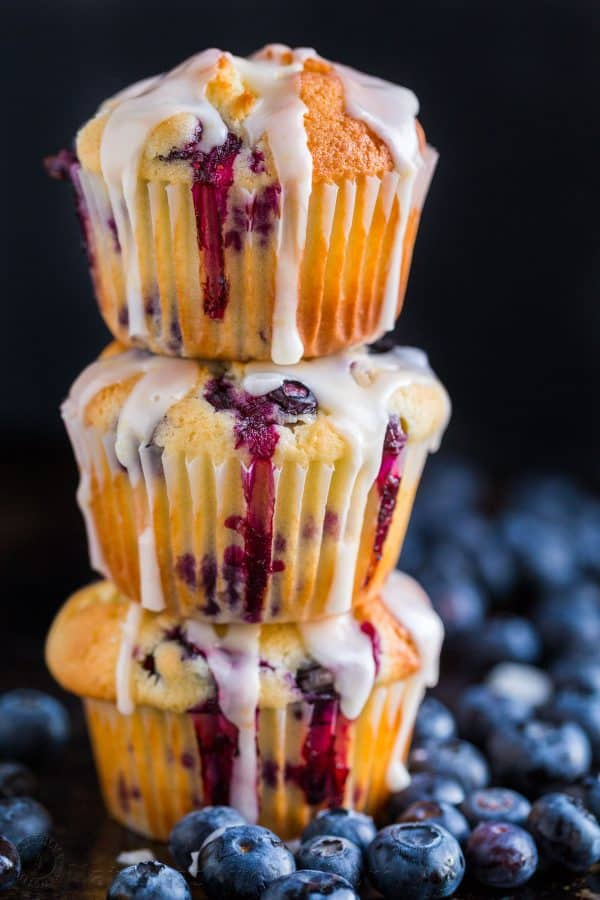 Blueberry Muffins glazed and stacked surrounded by fresh blueberries