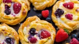This Cream Cheese Danish recipe is so easy to make. The cheese danish filling tastes just like cheesecake and the fresh berries and lemon glaze add a bright pop of flavor. This puff pastry recipe always disappears fast!