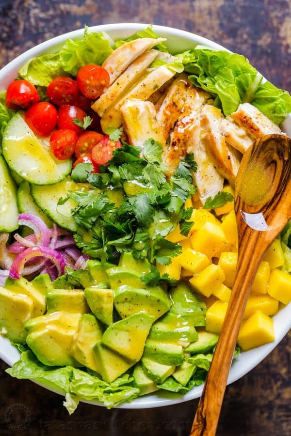 Ingredients for chicken mango avocado salad arranged in bowl with spoon