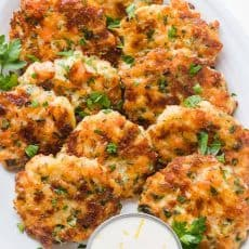 Cheesy Shrimp Cakes aka Shrimp Fritters with irresistible lemon aioli sauce. One of our favorite shrimp recipes! Biting into juicy shrimp, fritter style, is a real treat. The cheese creates an irresistible cheese pull inside and forms a golden crust on the outside. Watch the Video tutorial and you will just know; this recipe is GOOD | natashaskitchen.com