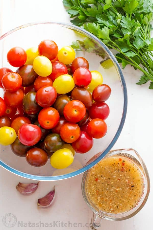 Ingredients for cherry tomatoes recipe with fresh cherry tomatoes, parsley, Italian dressing and garlic