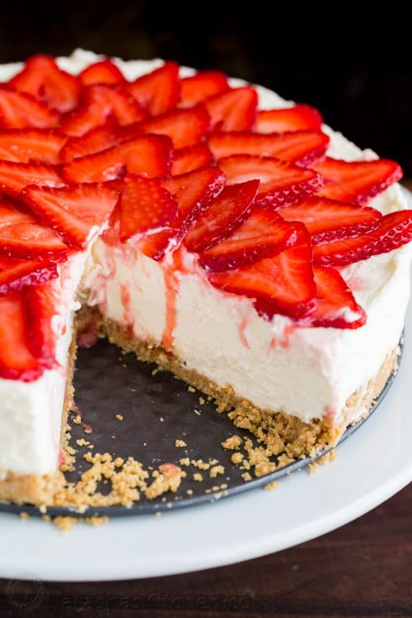 Sliced no bake cheese cake on a serving platter with strawberry topping