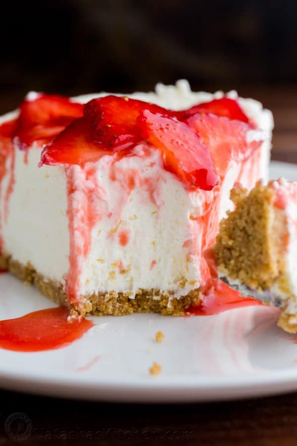 Slice of no-bake cheesecake recipe with strawberries and strawberry sauce