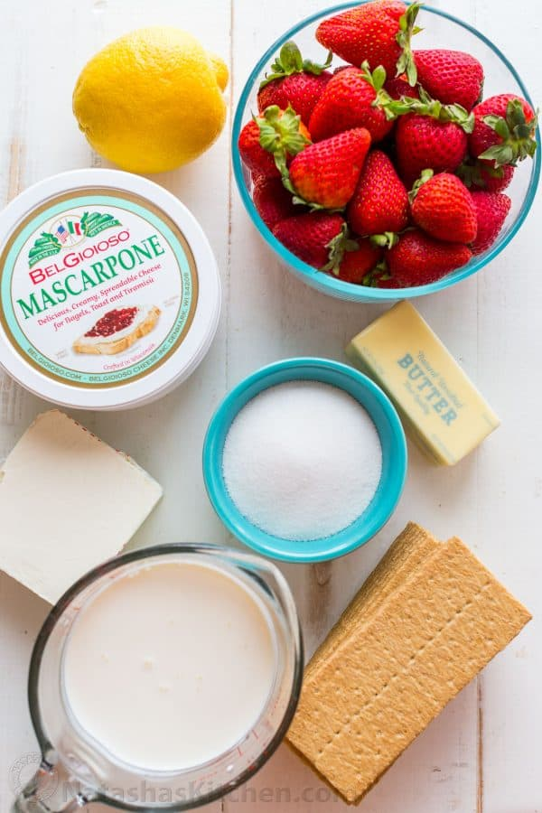ingredients for no bake cheesecake with strawberries including mascarpone, cream cheese, strawberries, lemon juice, graham crackers and whipping cream