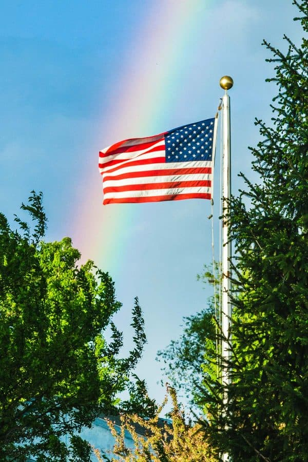Flag pole with rainbow in background