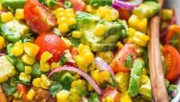 This Avocado Corn Salad is a bright and feel good salad that's loaded with grilled corn, creamy avocado, cherry tomatoes and the dressing gives it amazing fresh flavor. This is a crowd pleasing corn salad that always dissapears fast! | natashaskitchen.com