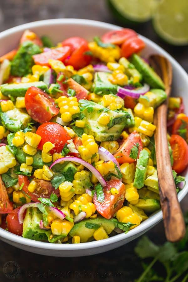 Fresh Corn salad with avocado mixed together in a bowl
