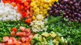 Cowboy Caviar ingredients arranged in sections in a bowl ready to be mixed